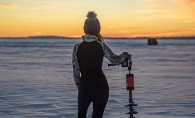 Standing with an ice auger on frozen lake