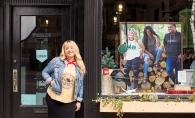 Sarah Schroeder, founder of Minnesota Made apparel company, poses outside a storefront displaying some of her products