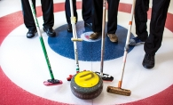 Curlers at the St. Croix Curling Center hold their brushes near a stone.