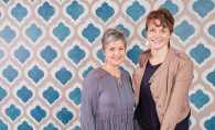 The two women behind Gypsy Mint Stencil Co. pose in front of some stencil work.