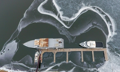 Boats surrounded by ice on the water on the St. Croix River at the Hudson Dike