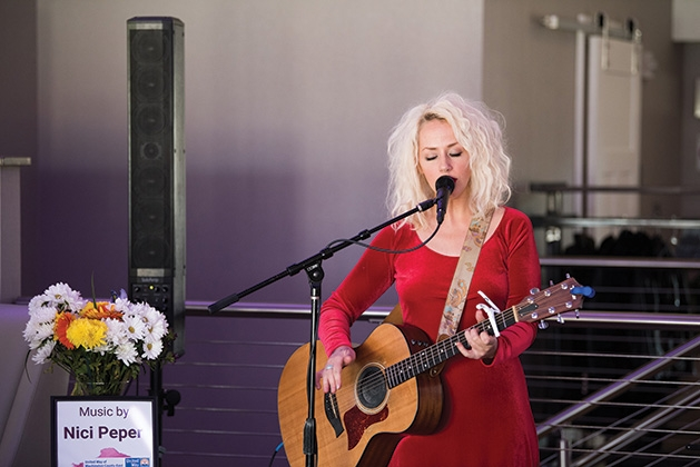 A woman plays guitar and sings at United by the Vine 2019.