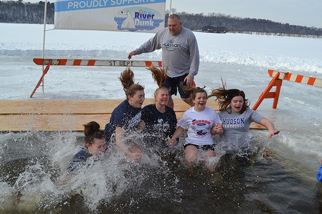 A group of girls jump into the water at the St. Croix River Dunk
