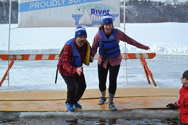 Two people jump into the water at the St. Croix River Dunk
