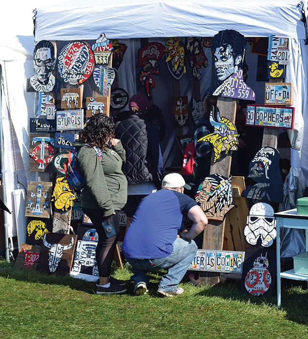 Attendees look at art at the Rivertown Fall Art Festival 2019