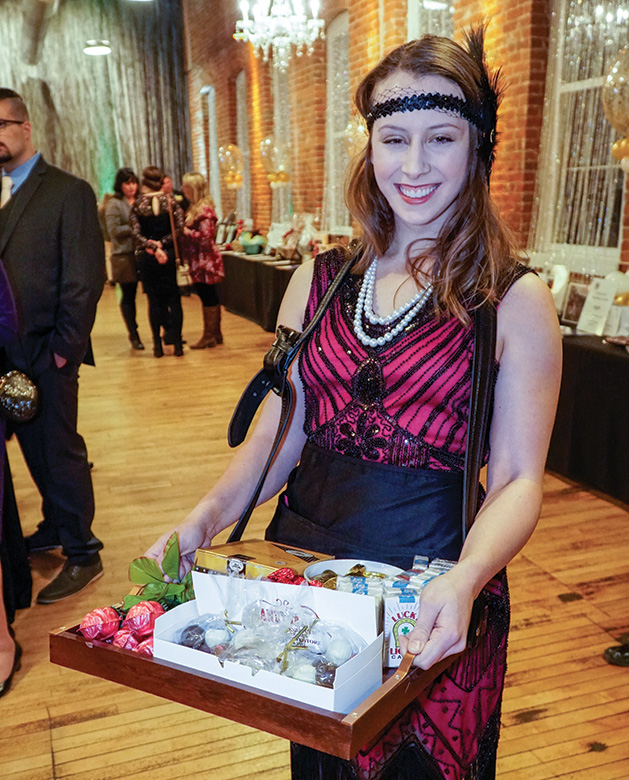 A woman holds goodies from the Zephyr Theatre at the Stillwater Chamber Gala.