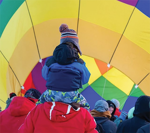 A child on an adult's shoulders watched balloons at the Hudson Hot Air Affair 2020.