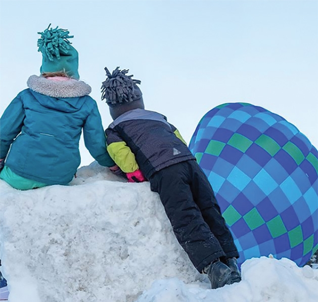 Children on a snow hill watch balloons at the Hudson Hot Air Affair 2020