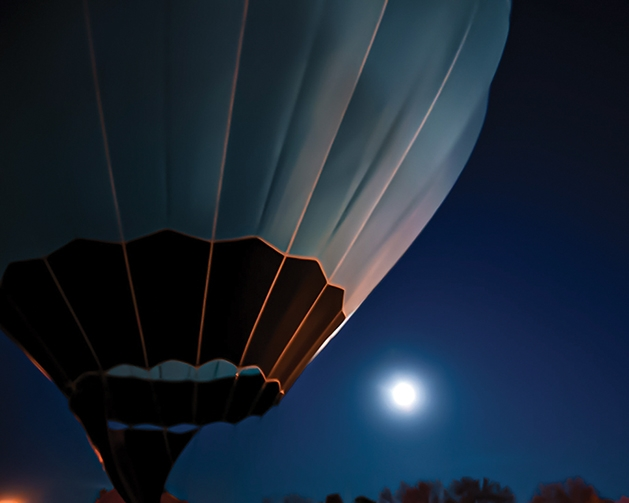 Hot air balloon illuminated by moonlight