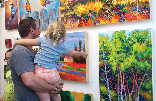 A father and daughter admire art at the Spirit of the St. Croix Art Festival, one of many local fall art festivals.