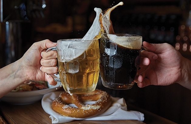 Two drinkers clink two glasses of the best local Oktoberfest beers.