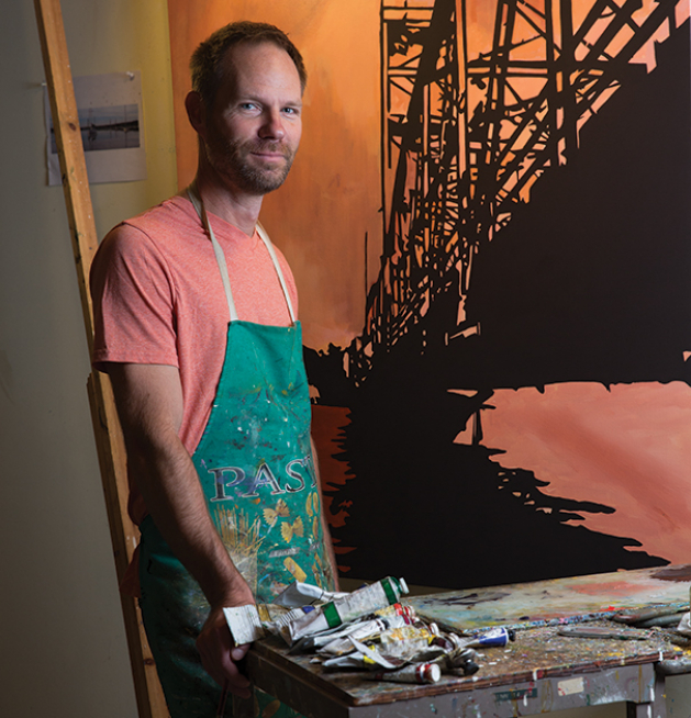 Artist Michael Slagle stands behind a table with painting supplies.