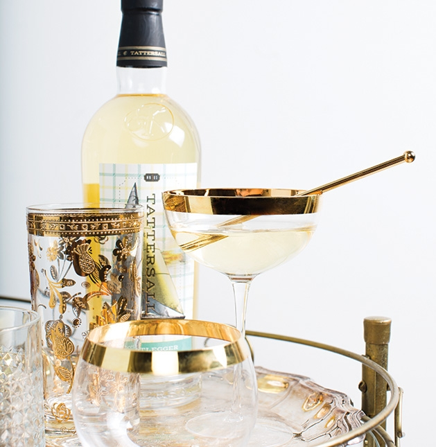 A bottle of liquor from Tattersall Distilling sits on a bar cart with an aperitif.