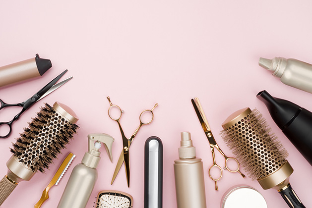 A row of various beauty products on a pink background.