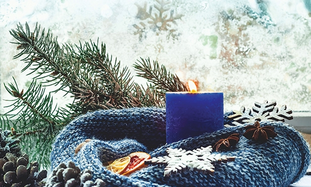 A blue scarf wrapped around a blue candle with other holiday decor.