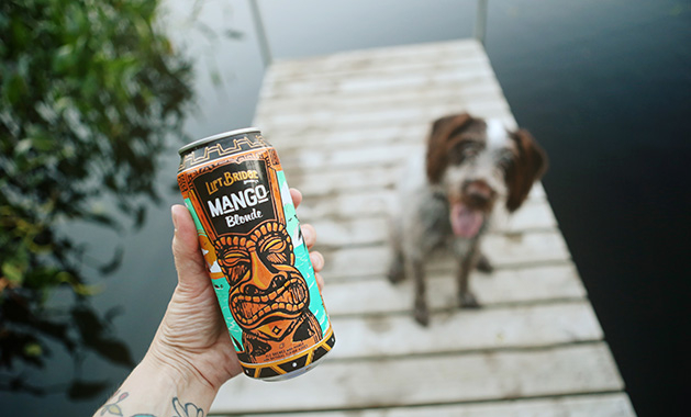 A person holds a can of Lift Bridge Mango Blonde while a dog sitting on a dock watches.