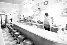 A waitress stands behind the bar area at Not Justa Cafe in this black and white photo
