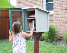 A little girl looks at the books in a Little Free Library.