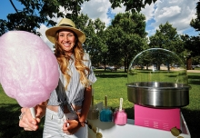 Sarah Kubler, founder of Confection Cotton Candy, stands by a cotton candy cart, available for events in Wisconsin and Minnesota.