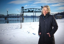 Charlene Roise, author of The Saga of the Stillwater Lift Bridge,  stands with the bridge in the background.