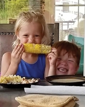 Two children smile while eating sweet corn in this Lens on St. Croix Valley winning photograph.
