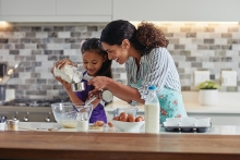 A mother and child cook together.
