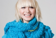 A blonde woman wearing a blue scarf.