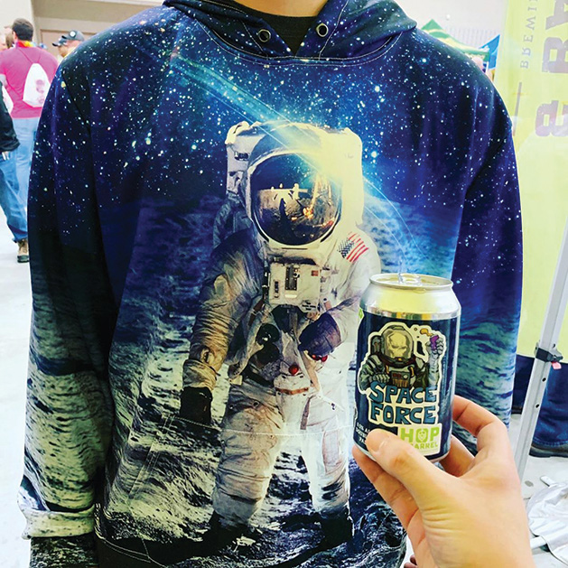A person in an astronaut hoodie holds a beer from Hop & Barrel Brewing
