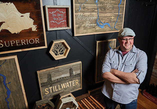 Tom Velure stands before some of his custom wood lake maps at Smith + Trade Mercantile
