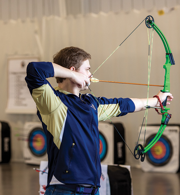 A student on the St. Croix Preparatory Academy archery team pulls back for a shot.