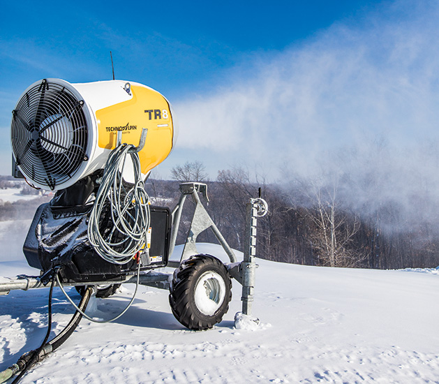 A snow machine blows snow onto a ski hill