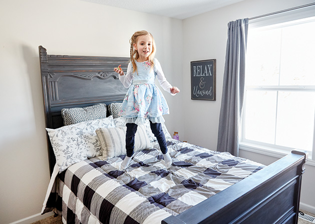 One of the Eikes' grandchildren jumps on a bed.